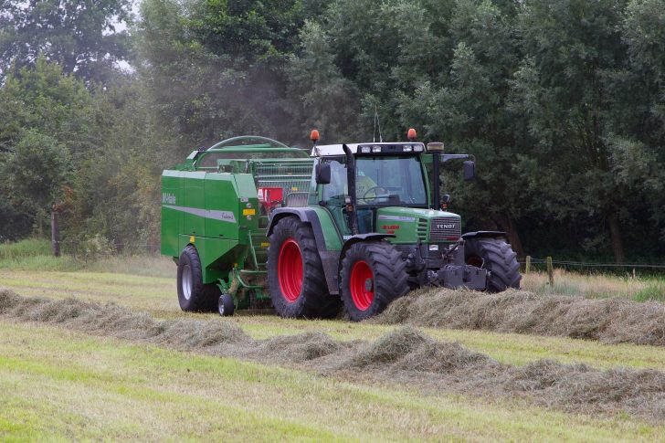 EDE, THE NETHERLANDS - AUGUST 22. Farmer making hay bales on a field near Ede, The Netherlands on August 22, 2013.
